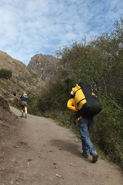 A steep section of trail. A lightly equipped hiker is visible at left and a Peru Treks porter at right